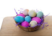 Wicker basket of colored eggs and straw — Stock Photo