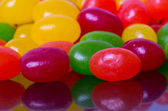 Closeup of jelly beans reflected in glossy black — Stock Photo