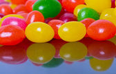 Jelly beans reflected in glossy black — Stock Photo