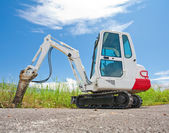 Small caterpillar tractor stands on the asphalt against the blue — Stock Photo