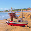 The little toy boat stands on sandy beach - Stock Photo