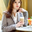 Young brunette woman is drinking coffe — Stock Photo