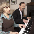 Seniors playing piano duet — Stock Photo