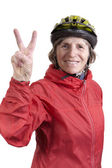 Happy retired woman in bicycle helmet showing peace sign — Stock Photo