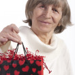 Royalty-Free Stock Photo: Senior woman raising gift bag