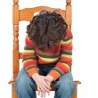 Sad child sitting on a chair isolated - Stock Photo
