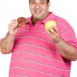 Fat man deciding between a candy and an apple — Stock Photo #9424584
