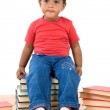 Baby sitting on a pile of books — Stock Photo