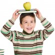 Adorable child studying with books and apple in the head — Stock Photo #9431848
