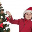 Beautiful child with Christmas trees — Stock Photo #9432356