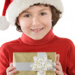Adorable boy with red hat of Christmas and one gift — Stock Photo