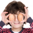 Adorable Child with two eggs on his eyes - Stock Photo