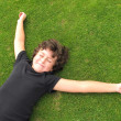Photo: Happy child resting on grass