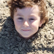 Child buried in the sand — Stock Photo #9433395