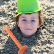 Child buried in the sand — Stock Photo