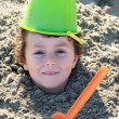 Child buried in the sand - Stock Photo