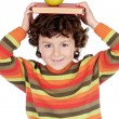 Adorable child studying with books and apple in the head — Stock Photo #9433622