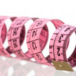 Pink tape measure with reflection on the floor - Stock Photo