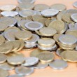 Many coins on wooden surface — Stock Photo #9438691