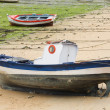 Boat and little fishing ship on the sand with low tide - Stock Photo