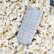 Popcorn and remote control — Stock Photo