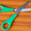 Green scissors on a table - Stock Photo
