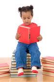 ребенка читать, сидя на кучу книг — Стоковое фото