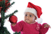 Baby girl playing with christmas tree — Stock Photo