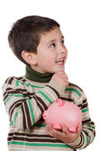 Adorable child thinking what to buy with their savings — Stock Photo