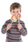 Child eating two lollipops — Stock Photo