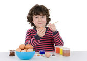 Child adorable adorning Easter eggs — Stock Photo