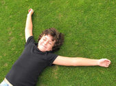 Happy child resting on grass — Stok fotoğraf
