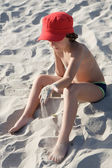 Boy sitting on the sand from the beach — Stock Photo