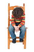 Triest kind zittend op een stoel geïsoleerd — Stockfoto