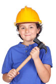 Beautiful child with yellow helmet and hammer — ストック写真