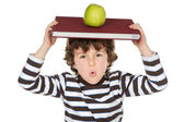Adorable child studying with books and apple in the head — Foto de Stock
