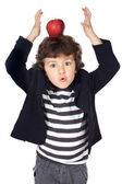 Adorable child with an apple in the head — Stock Photo