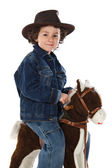 Child mounted on a wooden horse — Stock Photo