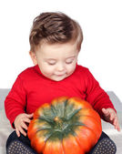 Beautiful blond baby with a big pumpkin — Stock Photo