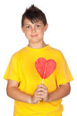Funny child with yellow t-shirt with a big lollipop — Стоковое фото