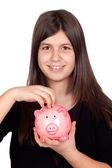 Adorable preteen girl with a piggy-bank — Stock Photo