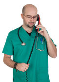 Doctor talking on a red phone — Stock fotografie