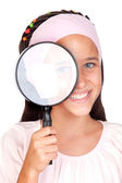 Little girl with a large magnifying glass — Stock Photo