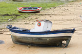 Boat and little fishing ship on the sand with low tide — Stock Photo