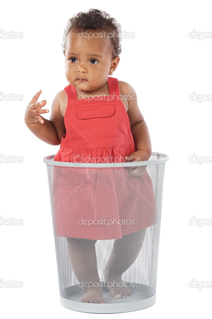 Beautiful African baby dressed in red inside a trash — Stock Photo #9431300