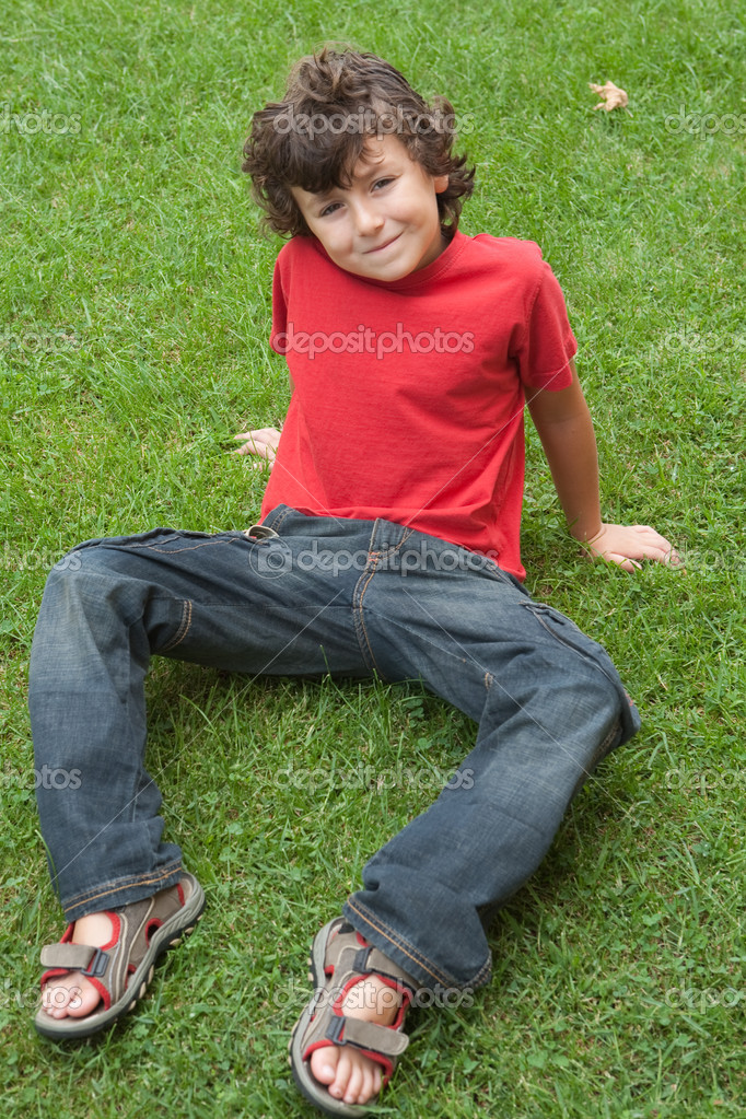 Happy child sitting on the grass with red shirt — Stock Photo #9432250