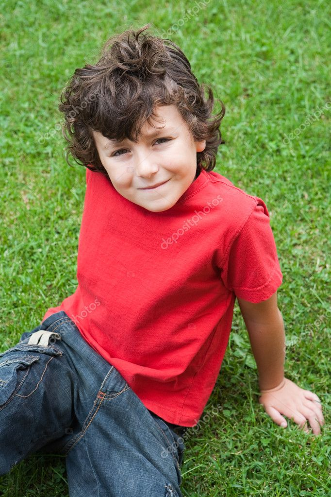 Happy child sitting on the grass with red shirt — Stock Photo #9432251