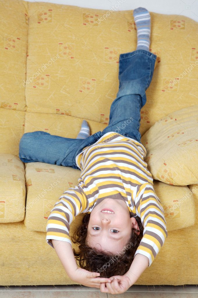 Small handsome boy lying down on the sofa at home — Stock Photo #9433060