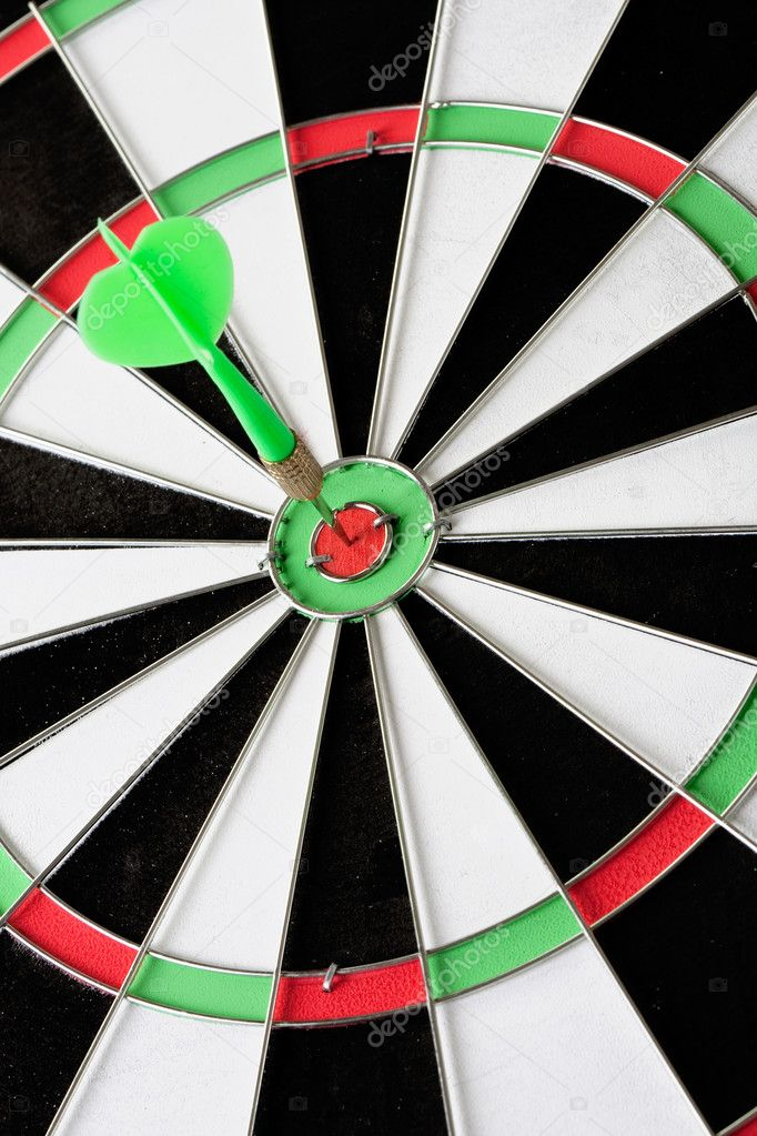 Green dart punctured in the center of the target — Stock Photo #9437889