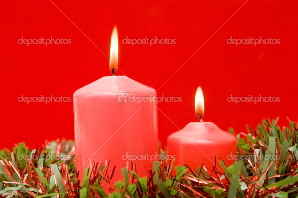 Red candles of Christmas lit on a over red background — Stock Photo #9438161